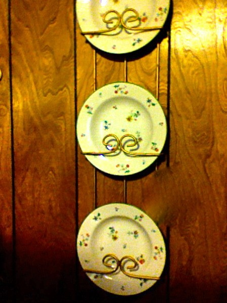 3 China plates hanging on wall in plate rack