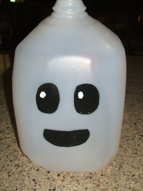 Finished milk jug ghost. Black eyes and black mouth painted on white milk jug.