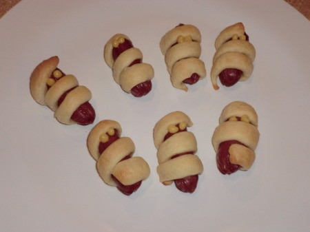 Croissant wrapped sausages as a Halloween appetizer.