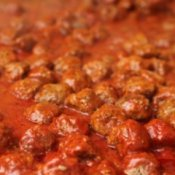 Meatballs cooking in sauce.