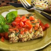 A savory egg and sausage casserole topped with tomatoes.