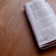 A newspaper on a wood table.