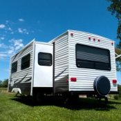 Saving Money on Summer Travel, A travel trailer at a campsite.