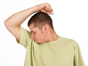 Man in Green Shirt Smelling His Underarm