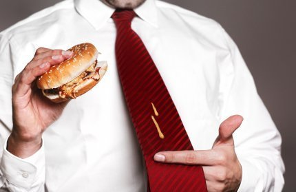 Man Holding Burger with Mustard Stain on his Tie