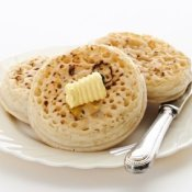 Crumpets on a plate with butter on them.