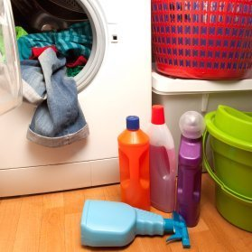Open front load washer with clothing hanging out. There are laundry product bottles on the floor and baskets stacked nearby.