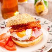 Ham, bacon, and egg sandwich on a crusty bun.