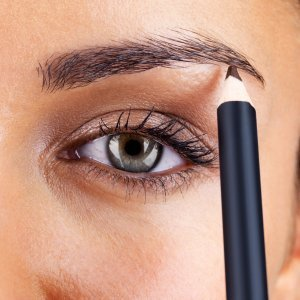 A woman using an eyebrow pencil.