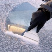 Removing Ice from Your Windshield, Gloved hand scraping icy windshield.