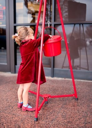 Girl in a red coat giving to the Salvation Army.