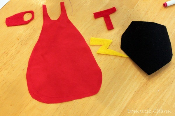Red cape and super hero turkey emblems cut out of felt.
