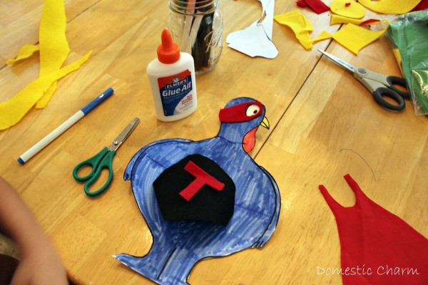 Turkey cutout, colored in blue with cape and eye mask placed on top ready to be glued.