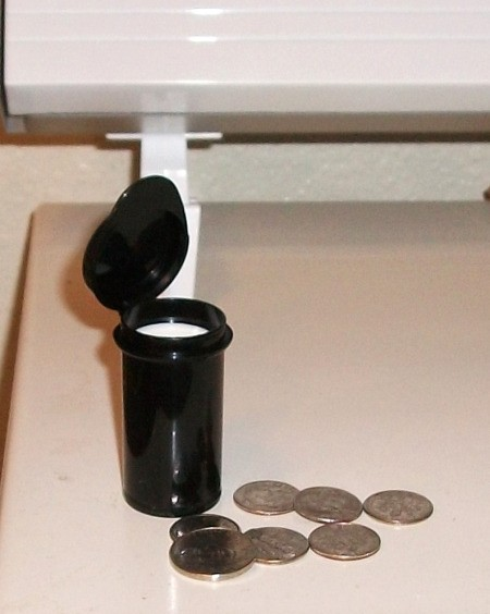 Black test strip container with some coins in front
