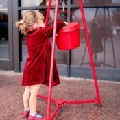 Little girl giving to Salvation Army.