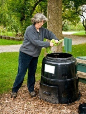 Picture of a woman using a composter.