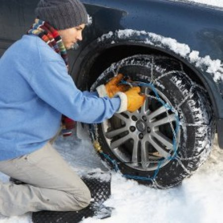 Preparing Your Car for Winter, Young man putting snow chains on his car tire