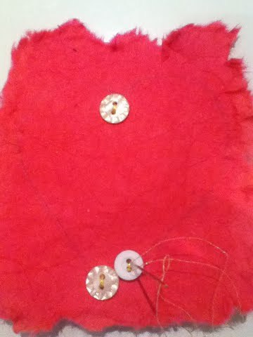 Button Love Christmas Present - white buttons being sewn onto red material