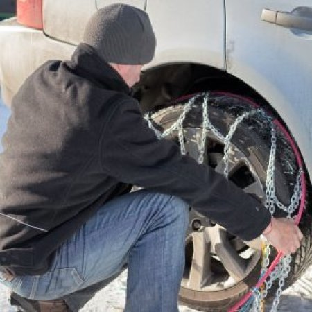 Putting on Snow Chains in Bad Weather, Man putting on snow chains.