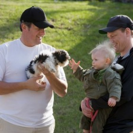 A man introducing his dog to a father and child.