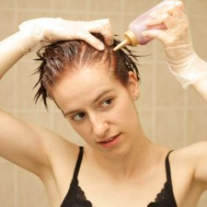 A woman dying her own hair.