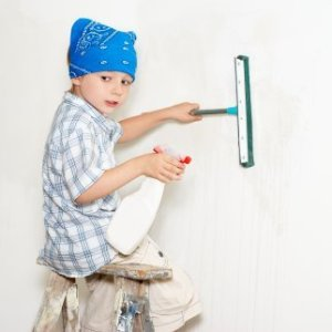 Young boy sitting on a step ladder cleaning a wall.