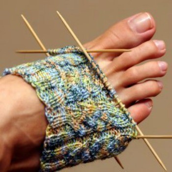 Partially knit sock over a woman's foot with needles in place.