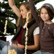 Kids making popcorn garland.