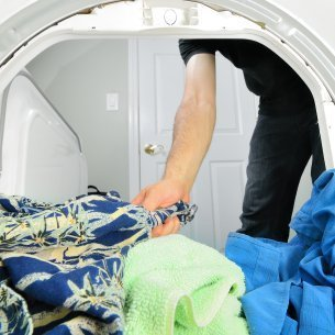 Removing Melted Crayon from Dried Clothes, Man removing clothes from the dryer.