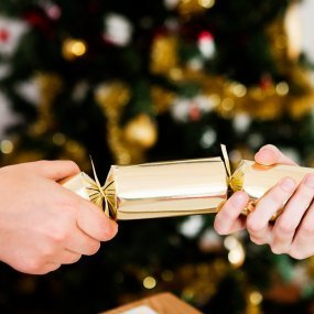 Homemade Christmas Crackers, Two people pulling apart a Christmas cracker.