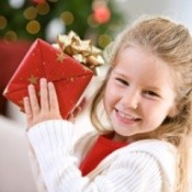 A girl holding a red present.