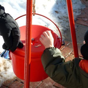 A child putting coins in a donation bucket.