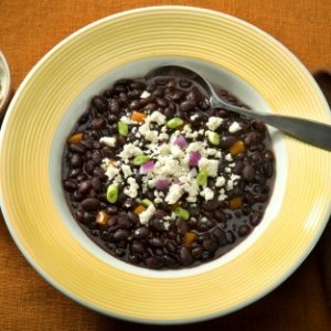 A bowl of hearty black bean soup with a sprinkling of cheese.