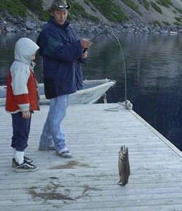 Man and a boy catching a fish on a dock.