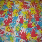 Homemade wrapping paper made with different colored handprints in paint.