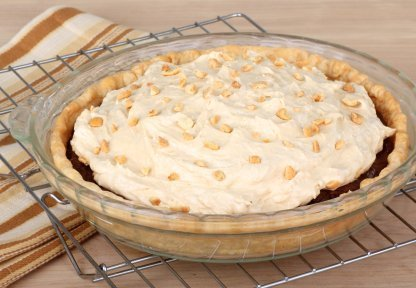 A whole uncut peanut butter pie on a cooling rack.