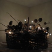 Lighted holiday basket with pinecones and twigs