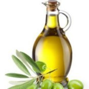 Bottle of olive oil with olive branch in the foreground.