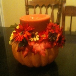 Stryofoam pumpkin with candle and artificial flowers.