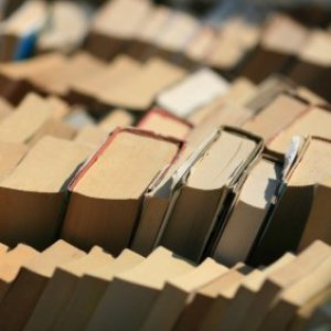 Saving Money On Books, Stacks of old books at a flea market or used book sale.