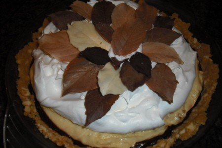 Whole pie with chocolate, peanut butter, and whipped cream layers topped with dark and white choclate leaves