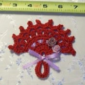 A small red crocheted fan.