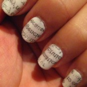 Newspaper print applied to nails.