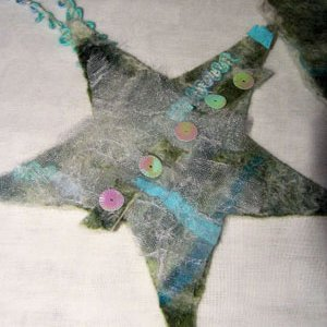 A Christmas star ornament made from felt and embellishments.