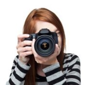 A girl in a striped shirt holding a camera to her eye.