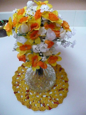 Plarn centerpiece mat with vase of silk flowers.