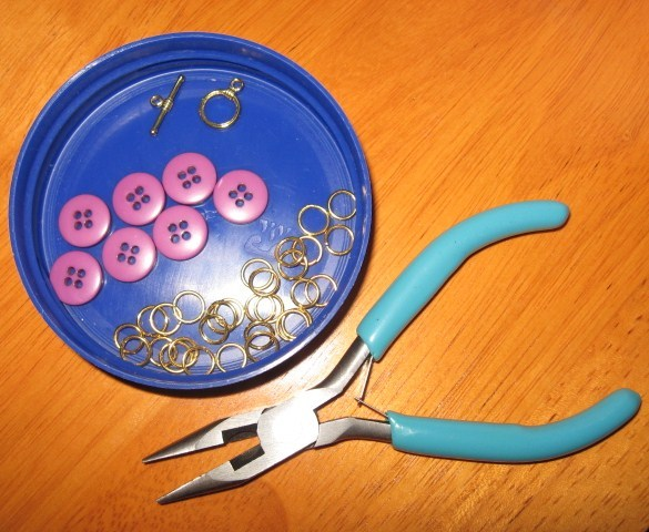 Buttons, jump rings, toggle clasp, and needle nose pliers.