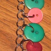 Buttons attached to flat link chain with jump rings.