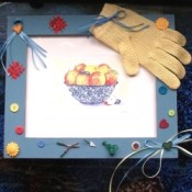 Finished framed print with embellishments, such a a glove, ribbons, buttons, and tiny trowel, etc.