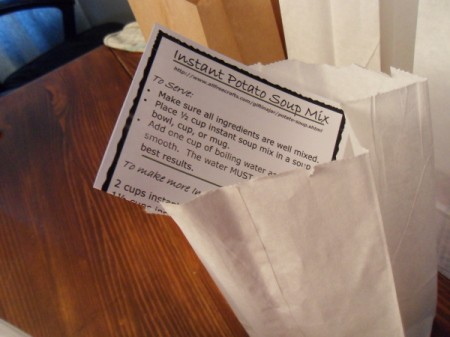 Adding recipe card to white lunch bag.